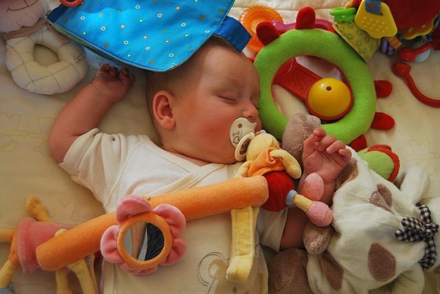miminko v postýlce plné hraček